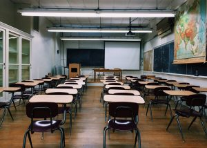 A classroom with many desks and several blackboards