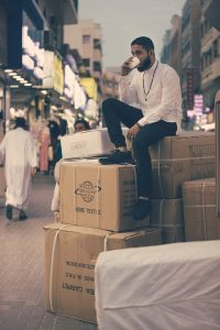 Man sitting on cardboard boxes on a street