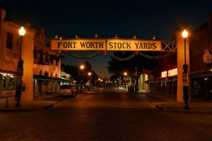"An empty street, buildings on both sides and a ""Fort Worth Stock Yards"" sign decorated for Christmas"