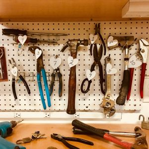 Different hand tools hanging and lying on a shelf