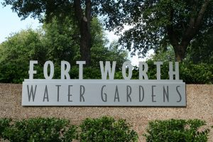 "A ""Fort Worth Water Gardens "" sign surrounded by trees - a good place to spend family time in Fort Worth"