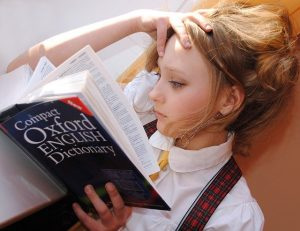 Girl reading an Oxford dictionary