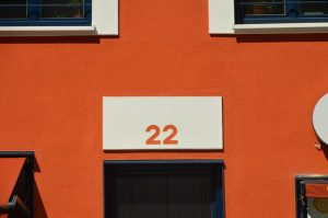 House number 22 on an orange building after summer upgrades for your home