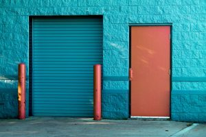 Blue Garage door and an orange door next to it