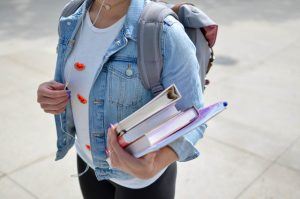 girl holding books and wearing a backpack