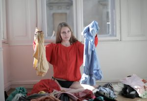 woman-in-red-long-sleeve-shirt-holding-her-clothes