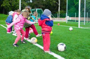 Couple of kids kicking footballs