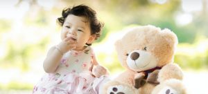 -baby on the grass and a toy bear