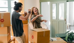 a couple laughing, packing for the move, cardboard boxes around them