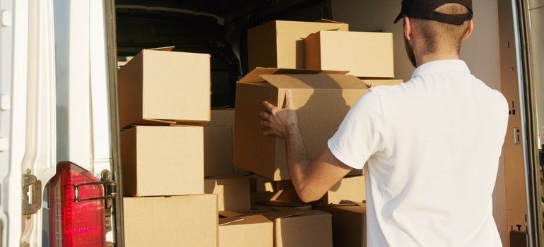A man loading boxes onto the moving truck