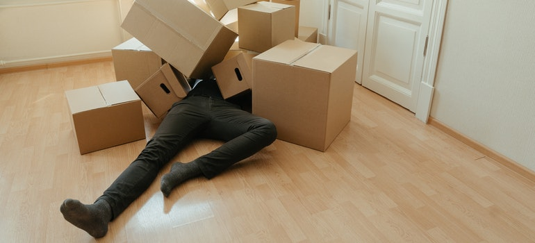 A man lying on the floor covered in cardboard boxes
