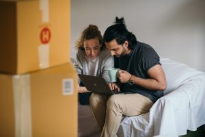 a couple sitting and drinking coffee while searching online about moving from Carrollton to Irving