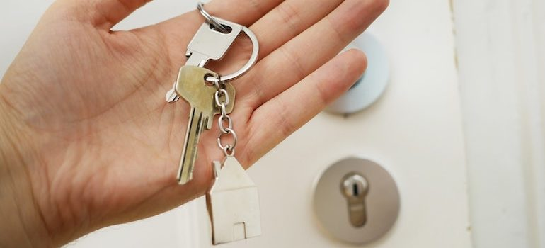 hand holding keys in front of entrance doors