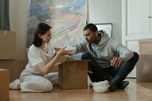 a couple sitting on the floor while putting items inside a box