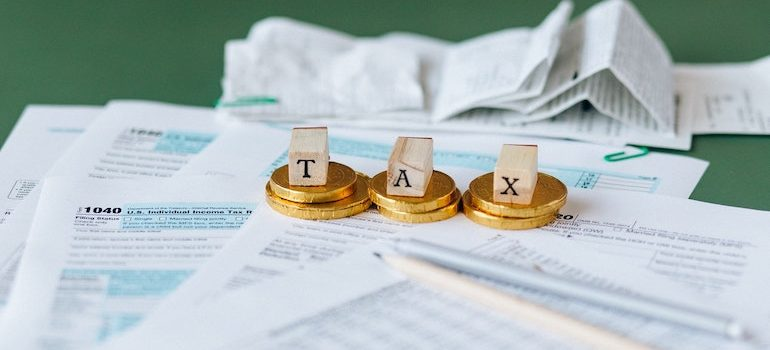 coins on tax forms and 3 wooden cubes that spell TAX