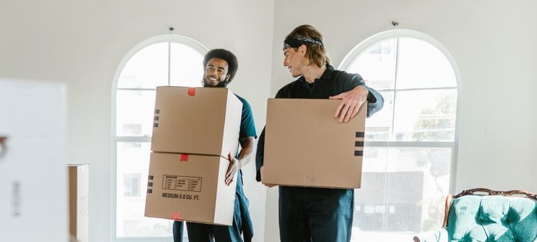 Two people moving boxes