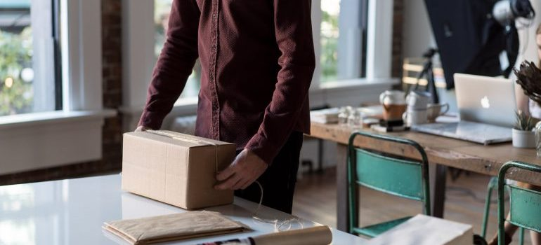 A person packing the box for moving