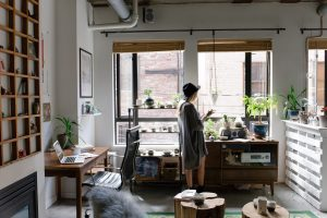 A woman in dark dress and with a hat on is standing in the room full of shelfs, tables, laptop, pot plants, wall pictures, coffee cups and lot other small things.