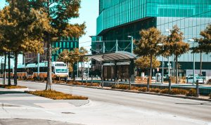 A road in Dallas, buildings with glass surfaces and trees, and a trees and public transport tram that you can use after moving from Richardson to Dallas.