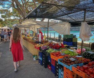 Woman in red dress walking and watching fruits and vegetables exposed on the stands on the right side.