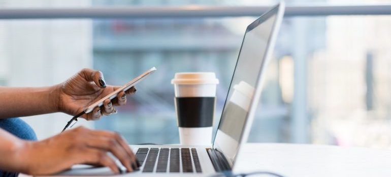 Person using phone and laptop computer while drinking coffee