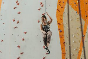 A girl with a smile hanging on the safety belts in front of the indoor rock for climbing.