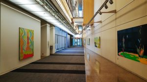 A hallway with yellow walls and modern art pictures in the interior of the University of Teas Dallas, in Richardson.