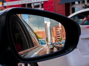 A rear mirror of the car with image of the downtown Dallas when you are moving from Dallas to Carrollton.