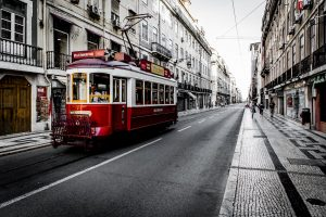 The red trolleybus runs along the narrow road between the buildings.