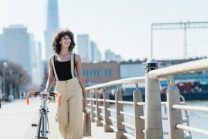 A girl holding a bicycle in one hand and a bag in another, is walking through the town with a smile on her face.