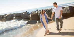 Man, and pregnant woman are walking on the sandy beach with waves and rock beside them, while discussing moving while pregnant.